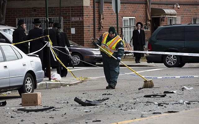 A worker clears debris from a fatal accident that claimed the lives of two expectant parents, Sunday, March 3, 2013, in the Brooklyn borough of New York. (photo credit: AP/John Minchillo)