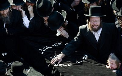 Members of Brooklyn's Satmar community grieve at the funeral of two expectant parents killed in a car accident. (John Minchillo/AP)