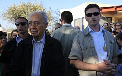 President Shimon Peres is surrounded by bodyguards during a visit to Kibbutz Kfar Aza in 2009 (photo credit: Tsafrir Abayov/Flash90)