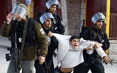 A Palestinian youth is arrested by Israeli Border Policemen following clashes with Israeli forces, February 2010. (Abir Sultan/Flash90)
