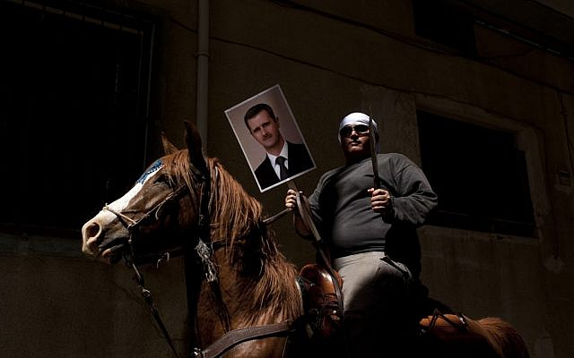 A Druze man holds aloft a machete and a portrait of Syrian President Bashar Assad during a rally in the village of Majdal Shams marking Syrian Independence Day, April 17, 2012 (photo credit: Matanya Tausig/Flash90)
