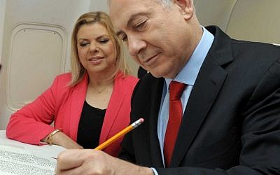 Benjamin Netayahu writes a letter in a Torah scroll on an airplane as he makes his way to visits the Czech Republic with his wife Sarah, May 17 2012. (photo credit: Avi Ohayon/GPO/Flash90)