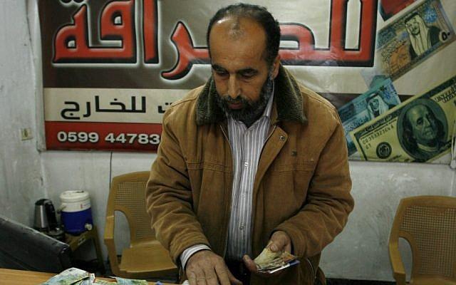 Illustrative photo of a Palestinian vendor counting shekels in Gaza. (photo credit: Abed Rahim Khatib/Flash90)