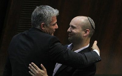 Finance Minister Yair Lapid, left, embraces Jewish Home leader Naftali Bennett in the Knesset, February 2013 (photo credit: Miriam Alster/Flash90)
