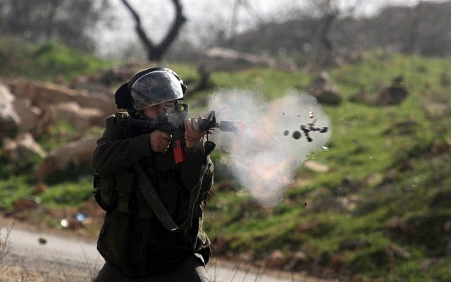 A soldier fires a smoke grenade at a demonstration at Birzeit University, February 15 (photo credit: Issam Rimawi/ Flash90)