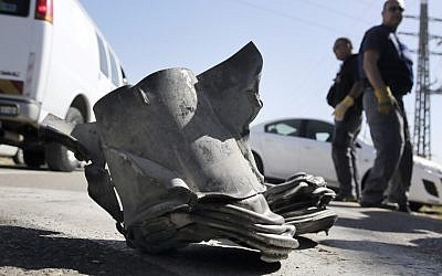 Israeli bomb technicians inspect the remains of a long-range rocket fired from the northern Gaza Strip at the coastal city of Ashkelon, Tuesday. (photo credit: Tsafrir Abayov/Flash90)