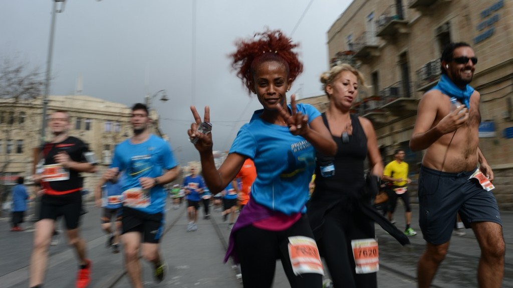 Participants smile through the pain during the Jerusalem marathon on Friday (photo credit: Flash90)