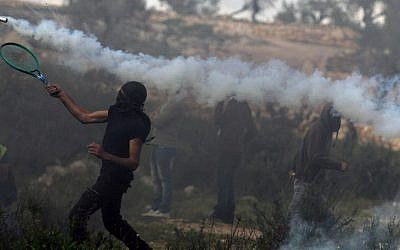 A Palestinian youth throws a tear gas canister back at an Israeli border guard using a tennis racket during clashes in the West Bank village of Bil'in, near Ramallah, on Friday. (photo credit: Issam Rimawi/Flash90)