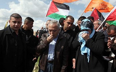 Palestinian Authority Prime Minister Salam Fayyad reacts after inhaling tear gas fired during clashes between hundreds of Palestinian youths and Israeli security forces in the West Bank village of Bil'in on Friday, following a large march which headed toward the security fence in support of Palestinian prisoners held in Israeli jails, and marking eight years of weekly protests which kicked off in February 2005. (photo credit: Issam Rimawi/Flash90)