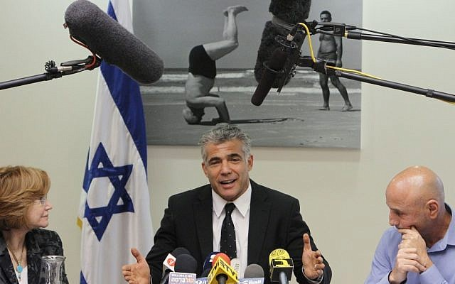 Yair Lapid sits underneath a photograph of the first prime inister David Ben-Gurion, as he attends a party meeting in the Knesset on March 04, 2013. (Photo credit: Miriam Alster/Flash90)