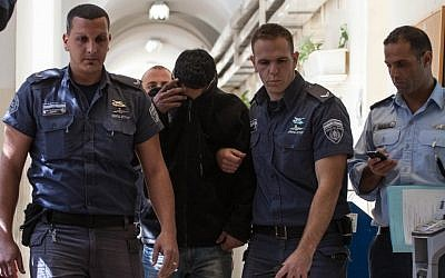A Jewish teenager who is suspected of participating in a stone-throwing attack on the vehicle of an Arab woman in Jerusalem is being brought to a judge in the Jerusalem Magistrates Court, on March 7, 2013. (photo credit: Flash90)