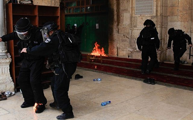 An Israeli policeman puts out flames on his foot from a molotov cocktail thrown at him from inside al-Aqsa Mosque on Friday. Behind him, a second petrol bomb burns (Photo credit: Sliman Khader/Flash 90)