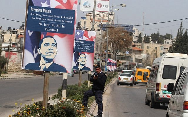 "A Palestinian policeman stands next to a poster informing US President Barack Obama, ""We have no 3G in Palestine,"" in the West Bank city of Ramallah in 2013 (photo credit: Issam Rimawi/Flash90)"