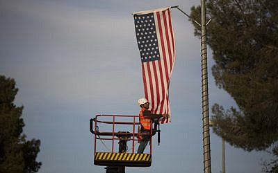 A Jerusalem municipality worker hangs an American flag near the President's House in Jerusalem on March 12, 2013, in preparation for the upcoming visit of US President Barack Obama. (Illustrative photo credit: Yonatan Sindel/Flash90)