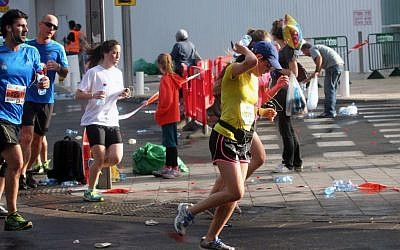 A woman pours water down her back during the Tel Aviv half marathon on Friday. (photo credit: Roni Schutzer/Flash90)