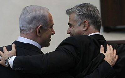 Israeli Prime Minister Benjamin Netanyahu embraces Yesh Atid leader Yair Lapid after addressing the Knesset ahead of the swearing-in of the new government, March 18, 2013. (Photo credit: Miriam Alster/FLASH90)