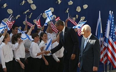US President Barack Obama and Israeli President Shimon Peres are greeted by children outside the President's Residence in Jerusalem on March 20, 2013. (photo credit: Amit Shabi/Flash90)