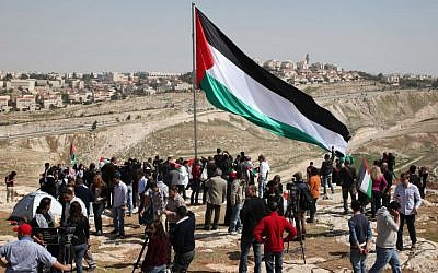 Palestinians set up the protest tent outpost in front of camera crews on March 20. (photo credit: Issam Rimawi//Flash90)