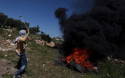 Palestinian protesters clash with Israeli soldiers near the West Bank village of Kafr Qaddum on Friday (photo credit: Issam RImawi/Flash90)
