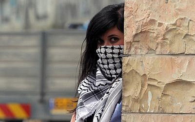 A masked Palestinian protester stands behind a stone wall during a rally marking Land Day at the main entrance to the Qalandia checkpoint, Saturday. (photo credit: Issam Rimawi/Flash90)