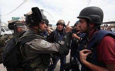 A Palestinian journalist confronts Israeli border police during a rally marking Land Day at the main entrance to the Qalandia checkpoint in the West Bank, Saturday. (photo credit: Issam Rimawi/Flash90)