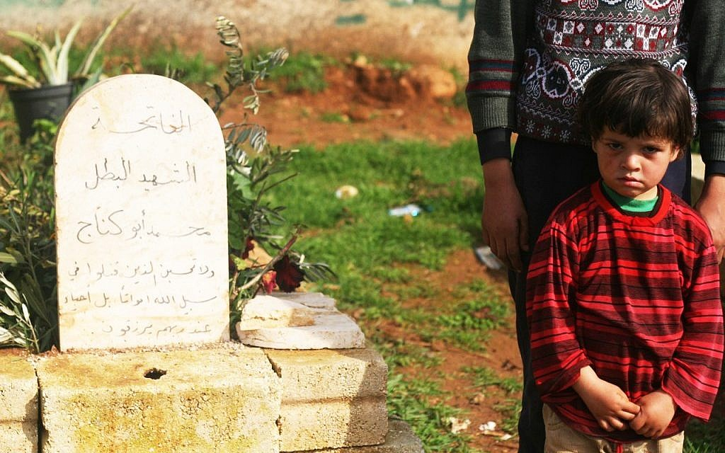 A young boy beside the grave of his relative, a fallen FSA soldier, in Qalaat al-Madik (photo: Eliyahu Kamisher)