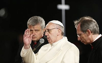 "Pope Francis delivers his blessing during the Via Crucis (Way of the Cross) torchlight procession celebrated in front of the Colosseum on Good Friday in Rome, Friday, March 29, 2013. Pope Francis is sitting in silent prayer during this year's Good Friday procession, which is re-enacting Christ's crucifixion and recalling the wars and ""violent fundamentalism"" that are devastating the Middle East today. The Good Friday procession at Rome's Colosseum is one of the most dramatic rituals of Holy Week, when Christians commemorate the death and resurrection of Christ. (photo credit: AP/Andrew Medichini)"