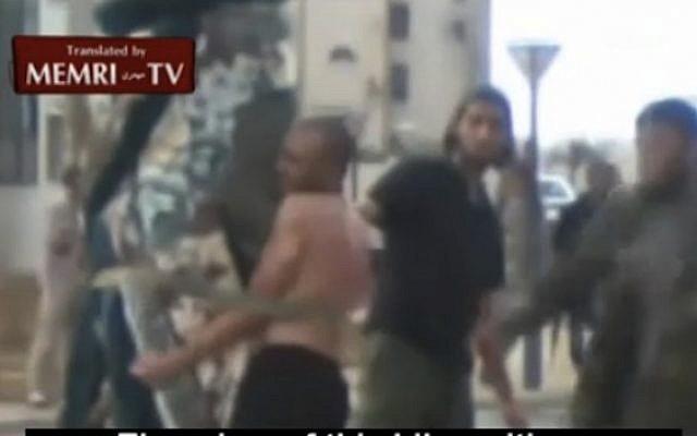Men in civilian attire administer lashings to a man in Sirte. (photo credit: MEMRI)