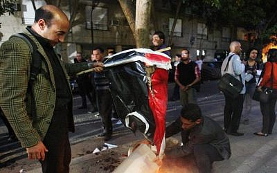 Egyptian protesters burn the Libyan flag during a protest in front of the Libyan embassy, in Cairo, Egypt, Monday, March 11, 2013 (photo credit: AP/Mohammed Abu Zaid)