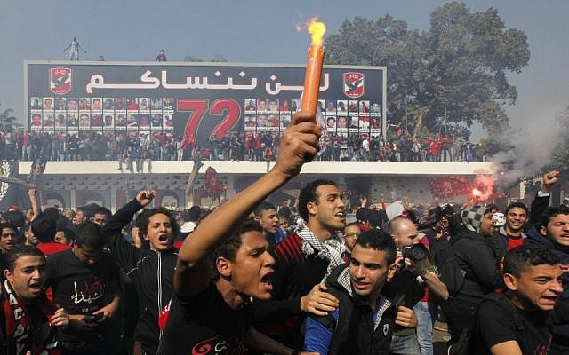 """Egyptian soccer fans of Al-Ahly club celebrate in front of their club in Cairo, Egypt, Saturday. An Egyptian court confirmed death sentences against 21 people for their role in a deadly 2012 soccer riot that killed more than 70 people in the city of Port Said. Banner at background showing some pictures of the victims with Arabic that reads, """"we will never forget you."""" (AP Photo/Amr Nabil)"""