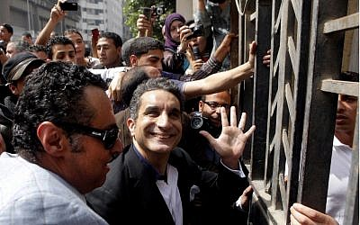 Popular Egyptian television satirist Bassem Youssef, who has come to be known as Egypt's Jon Stewart, waves to supporters as he enters the Egyptian state prosecutor's office in Cairo to face accusations of insulting Islam and the country's Islamist leader, Sunday. Government opponents said the warrant against such a high profile figure, known for lampooning Egyptian President Mohammed Morsi and the new Islamist political class, constituted an escalation in a campaign to intimidate critics. (AP Photo/Amr Nabil)