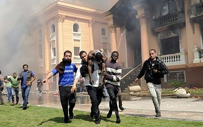 An injured security official is carried from a police officers club after protesters set fires following a court verdict in Cairo on Saturday. (photo credit: AP Photo/Mohammed Asad)