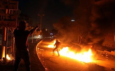 Egyptian protesters set tires on fire during clashes between supporters and opponents of Egypt's powerful Muslim Brotherhood near the Islamist group's headquarters in Cairo, Friday. (AP Photo/Khalil Hamra)