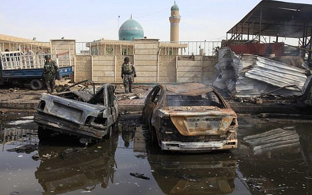 The scene of a car bomb attack in Baghdad, Iraq, Friday, March 29 (photo credit: AP/Karim Kadim)