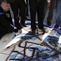 Palestinian activists vandalize a poster of US President Barack Obama in the West Bank city of Bethlehem, Monday, March 18, 2013. (photo credit: AP/Nasser Shiyoukhi)