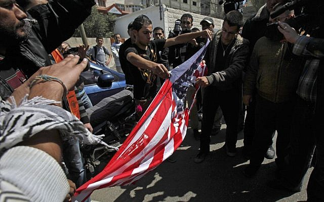 Palestinians rip an American flag during a protest against the visit of the U.S. President Barack Obama in Gaza City, Wednesday, March 20, 2013 (photo credit: AP/Adel Hana)