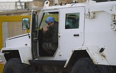 A UN peacekeeper from India waves while driving a UN armored vehicle as it leaves from the UNDOF Ziouani camp to cross to Syria at the Quneitra Crossing between Syria and the Israeli-controlled Golan Heights, Friday, March 8, 2013. (photo credit: AP/Ariel Schalit)