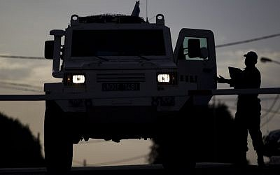 A UN peacekeeper checks a armored vehicle as it leaves from the UNDOF Ziouani camp to cross to Syria at the Quneitra Crossing between Syria and the Israeli-controlled Golan Heights,on  Friday, March 8, 2013. (photo credit: AP/Ariel Schalit)