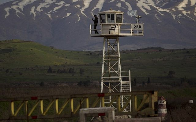Illustrative: A UN peacekeeper from the UNDOF force stands guard on a watch tower at the Quneitra Crossing between the Syrian and Israeli sides of the Golan Heights, on Friday, March 8, 2013. (AP/Ariel Schalit)
