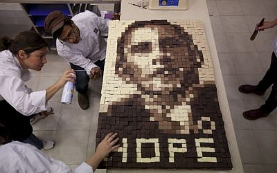 Students of Estella's school for bakery and pastry making, work on an image depicting US President Barack Obama made out of chocolate in Givat Shmuel, central Israel, on Monday, March 18, 2013. (photo credit: AP Photo/Ariel Schalit)