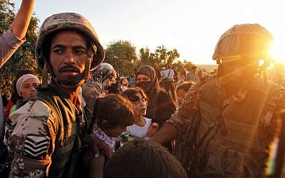File: In this Wednesday, Sept. 5, 2012 photo, newly-arrived Syrian refugee families receive food from the Jordanian military after they crossed the border from Tal Shehab in Syria, through the Al Yarmouk River valley, into Thnebeh town, in Ramtha, Jordan. (AP/Mohammed Hannon)