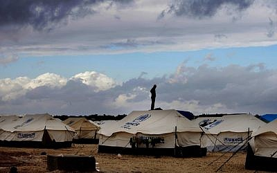 A Syrian refugee stands on top of a water tank at the Zaatari refugee camp, near the Jordanian-Syrian border, in Mafraq, Jordan, in January 2013 (photo credit: AP/Mohammad Hannon)
