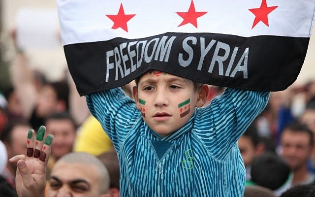 A Syrian boy waves the Syrian revolutionary flag during a commemorative celebration of the second anniversary of the Syrian revolution, in Amman, Jordan, March 16, 2013. (photo credit: AP/Mohammad Hannon)