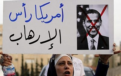 "A Jordanian protester holds a placard that reads ""America is the head of terrorism,"" during a protest near the Israeli Embassy against the visit by US President Obama to the region, in Amman, Jordan, Thursday, March 21, 2013. (photo credit: AP/Raad Adayleh)"