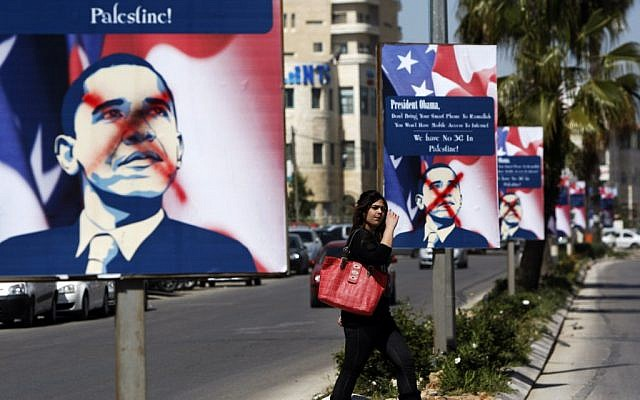 A Palestinian woman walks past vandalized posters of US President Barack Obama, in the West Bank city of Ramallah. (photo credit: AP/Majdi Mohammed)