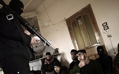 An instructor teaches Syrian rebels to use a rocket-propelled grenade launcher near Idlib, Syria, in March 2013. (photo credit: AP/Muhammed Muheisen)