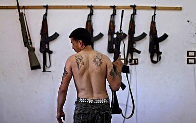 A Syrian rebel in an Aleppo arsenal (photo credit: AP/Muhammed Muheisen)