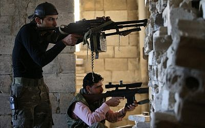 In this Tuesday February 26, 2013 file photo, Free Syrian Army fighters take their positions as they observe the Syrian army forces base of Wadi al-Deif, at the front line of Maaret al-Numan town, in Idlib province, Syria. (photo credit: AP/Hussein Malla, File)