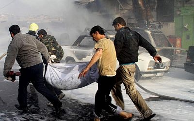 In this photo released by the Syrian official news agency SANA, Syrian citizens carry a dead body, at the scene where two mortar rounds exploded near an orphanage, at al-Boukhtyar area, in Damascus (photo credit: AP/SANA)