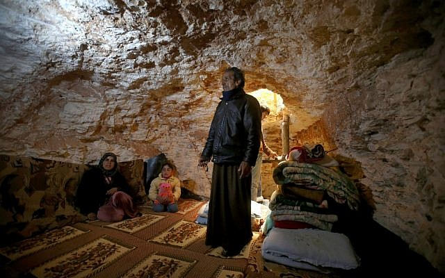 Sobhi al-Hamod, 60, lives with his family at an underground cave used for shelter from Syrian government forces shelling and airstrikes, at Jirjanaz, in Idlib province, Syria on Thursday. (photo credit: AP/Hussein Malla)